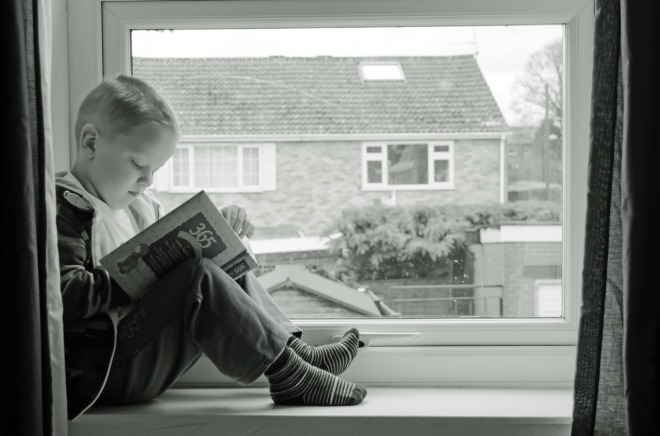 Little Boy Reading by The Window